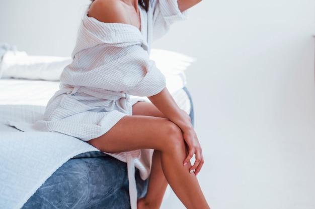 Abgeschnittenes foto einer frau in weißer kleidung, die auf dem bett im zimmer sitzt. schöne beleuchtung.