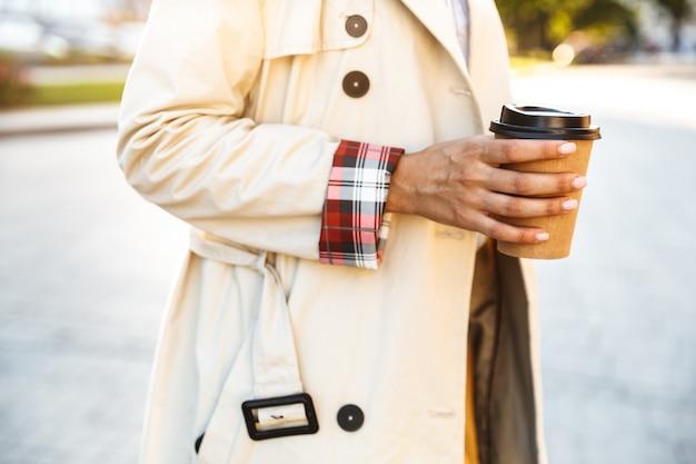 Abgeschnittenes foto einer jungen kaukasischen frau mit mantel, die kaffee zum mitnehmen trinkt, während sie auf der stadtstraße geht