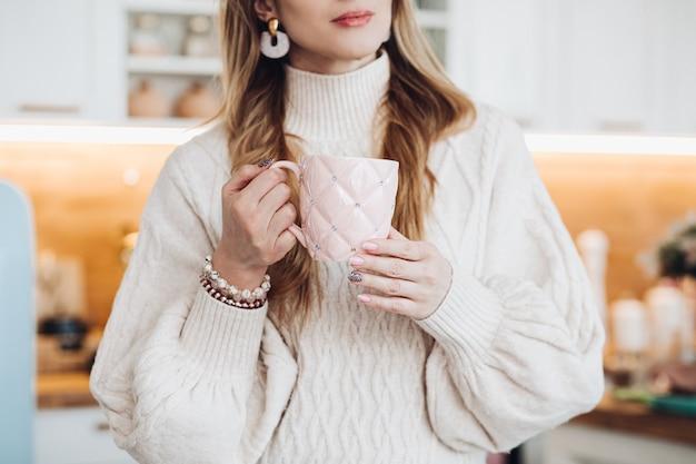 Abgeschnittenes foto einer jungen stilvollen frau in einem gemütlichen pullover und armbändern, die morgens in der küche eine schöne rosa tasse mit strasssteinen in ihren gepflegten händen hält.