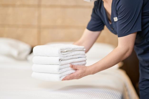 Abgeschnittenes foto eines dienstmädchens in uniform, das einen stapel sauberer handtücher im zimmer im hotel hält. hotelservicekonzept