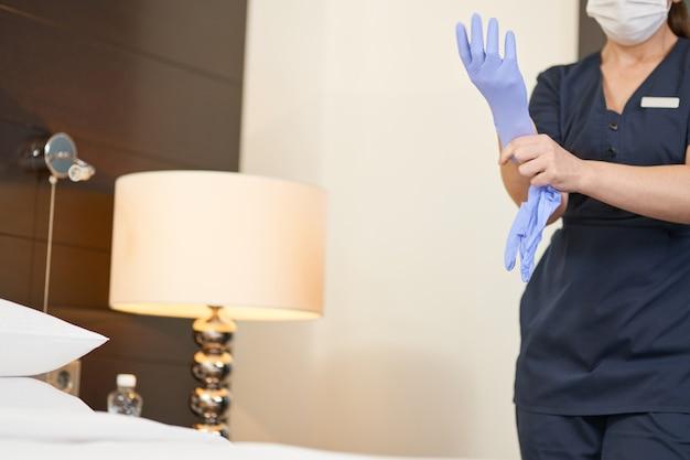 Abgeschnittenes foto eines dienstmädchens in uniform, das vor der reinigung schutzhandschuhe anzieht. hotelservicekonzept