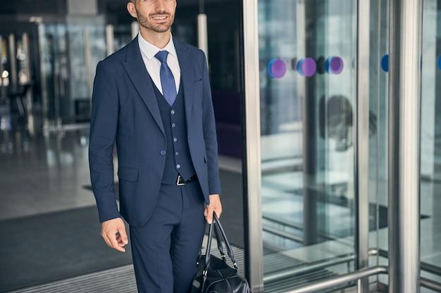 Abgeschnittenes foto eines gutaussehenden geschäftsmannes, der nach der ankunft seines flugzeugs lächelt, während er mit einer ledertasche spaziert