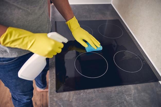 Abgeschnittenes foto eines mannes in handschuhen, der reinigungsmittel und spezialgummi verwendet, um schmutz zu entfernen