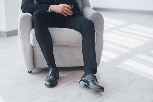 Abgeschnittenes foto eines stilvollen mannes im schwarzen anzug, der auf dem stuhl sitzt und ein glas mit alkohol hält.