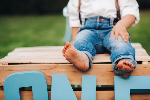 Abgeschnittenes foto eines süßen kindes, das weißes hemd und jeans trägt und mit nackten füßen im gras posiert