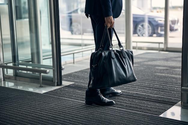 Abgeschnittenes foto eines unbekannten mannes, der in der nähe der glastür eines flughafens steht und eine schwarze ledertasche hält