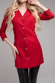 Abgeschnittenes foto im studio eines unkenntlich schlanken blonden models, das ein leuchtend rotes kleid mit dekorativen knöpfen und schwarzen lederleggings trägt.