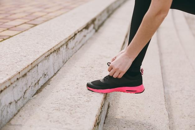 Abgeschnittenes foto, nahaufnahme von weiblichen händen, die schnürsenkel an schwarzen und rosa turnschuhen der frau beim training auf treppen im freien binden