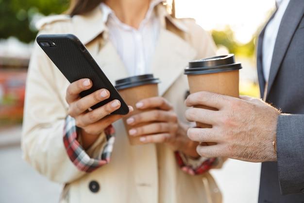 Abgeschnittenes foto von büroangestellten, mann und frau in formeller kleidung, die kaffee zum mitnehmen halten, während sie das mobiltelefon auf der straße der stadt benutzen