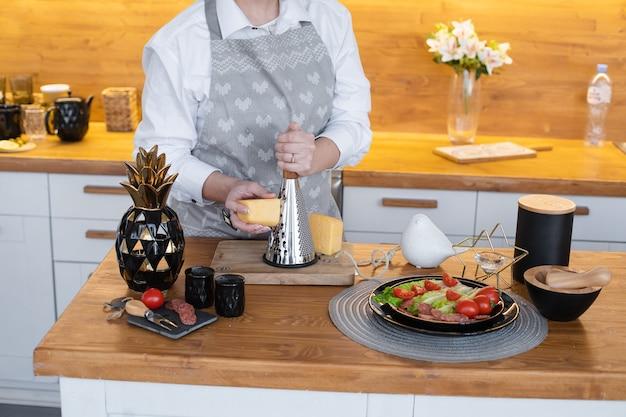 Abgeschnittenes foto von nicht erkennbarem koch, der käse auf einer reibe für eine mahlzeit reibt. frau, die zutaten für das abendessen auf der küchentheke aus holz zubereitet. frisches gemüse auf dem teller.