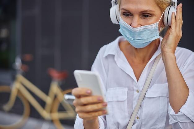 Abgeschnittenes kopfporträt einer lächelnden frau in schutzmaske, die auf den bildschirm ihres mobiltelefons schaut, während sie den kopfhörer mit einer hand berührt