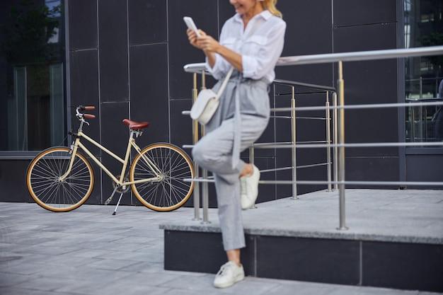 Abgeschnittenes kopfporträt eines retro-stadtfahrrads, bei dem eine frau in legerer geschäftskleidung davor steht, während sie das smartphone benutzt