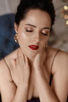 Abgeschnittenes porträt des model-mädchens mit perfektem trendigem make-up und vollen roten lippen, die mit geschlossenen augen posieren