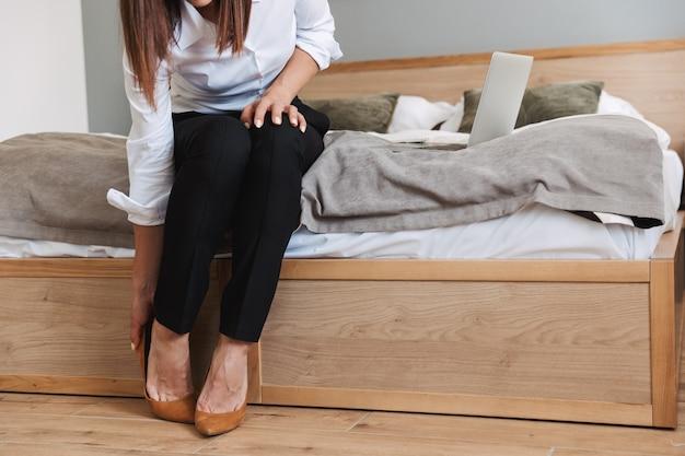 Abgeschnittenes porträt einer brünetten erwachsenen geschäftsfrau in formellem anzug, die ihre schuhe auszieht, während sie auf dem bett sitzt und einen laptop in der wohnung benutzt