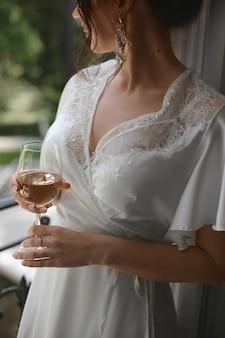 Abgeschnittenes porträt einer glücklichen jungen braut mit einem glas champagner am morgen vor der hochzeit ...
