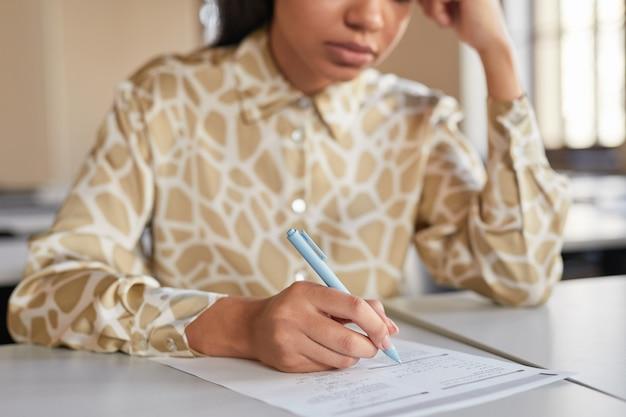 Abgeschnittenes porträt einer jungen afroamerikanischen frau, die in der schule eine prüfung ablegt, während sie am schreibtisch im college sitzt und nachdenkt, platz kopieren