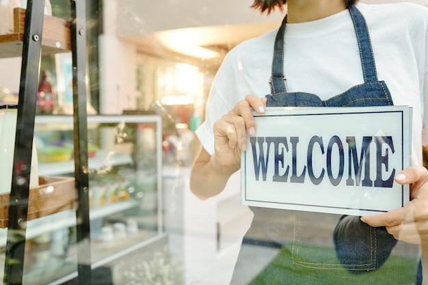 Abgeschnittenes porträt eines coffeeshop-baristas, der die kunden im inneren begrüßt