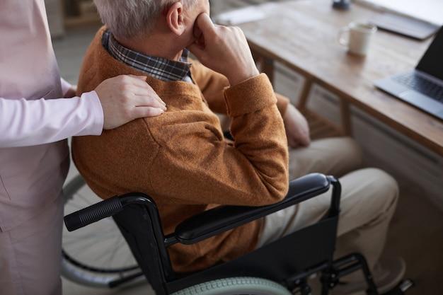 Abgeschnittenes porträt eines einsamen älteren mannes im rollstuhl im altersheim mit einer krankenschwester, die ihn tröstet, platz kopieren