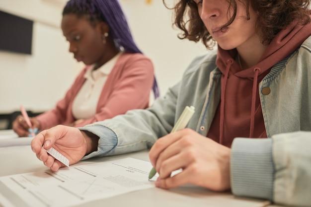 Abgeschnittenes porträt eines männlichen studenten, der während der prüfung in der schule cheat-notiz liest, platz kopieren