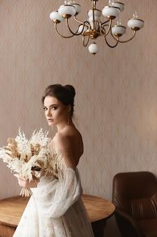 Abgeschnittenes porträt eines weiblichen models, das ein vintage-hochzeitskleid mit langen ärmeln im innenbereich trägt...