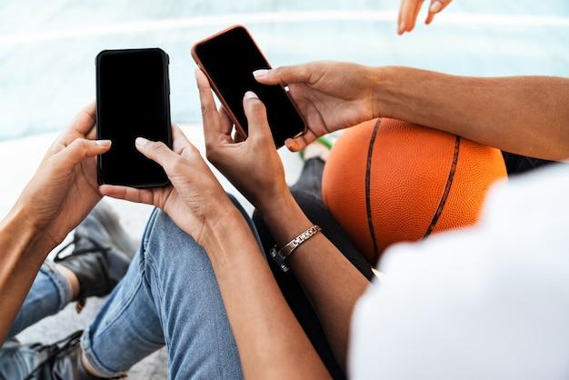 Abgeschnittenes porträt von zwei jungen afroamerikanischen mädchen in trendiger streetwear, die mit basketball und smartphones auf dem spielplatz sitzen
