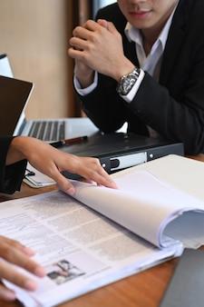 Abgeschnittenes team der personalabteilung, das den lebenslauf vor der bewerbung zum vorstellungsgespräch liest.