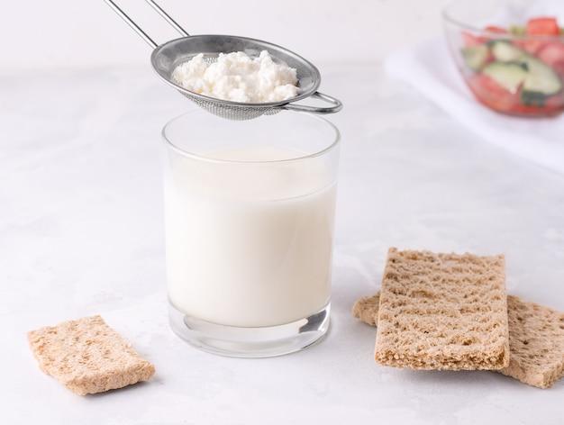 Abgesiebte milch aus kefirkorn. fermentiertes fermentiertes milchgetränk in einem glas.