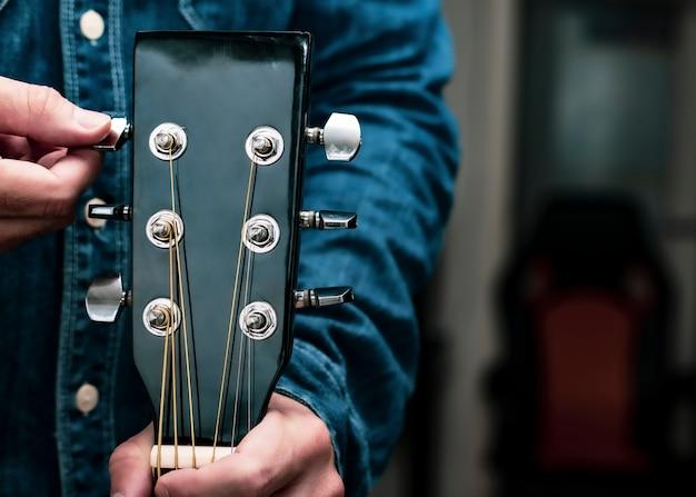 Abgestimmtes gitarrendetail, das die stifte am hals dreht. nicht erkennbarer mann, der schritt für schritt erklärt, wie man gitarrensaiten richtig einstellt. online-musikkurskonzept. innenleben.