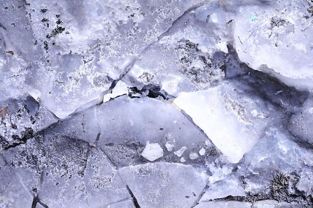 Abgestürzte blaue eisbetonoberfläche hintergrundtextur. abgestürzte eisbetonoberfläche hintergrundtextur. gefrorene eisfläche eines sees im sonnenuntergang