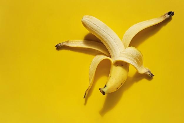 Abgezogene banane auf gelbem hintergrund