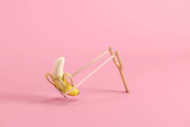 Abgezogene banane in einem katapult auf rosa hintergrund
