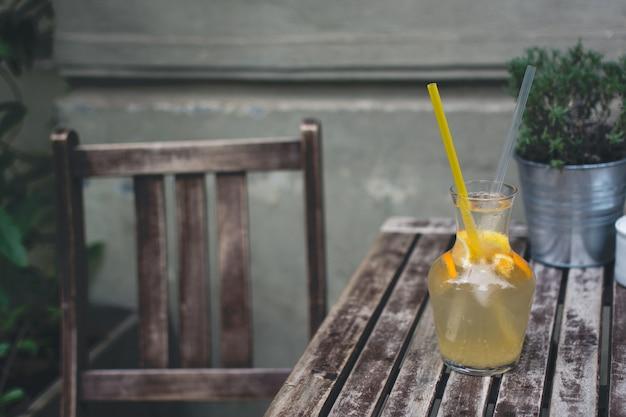 Abkühlende orangenlimonade auf einem hölzernen schreibtisch draußen