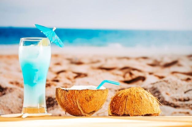 Abkühlendes blaues cocktail und kokosnussmilch auf sandigem strand