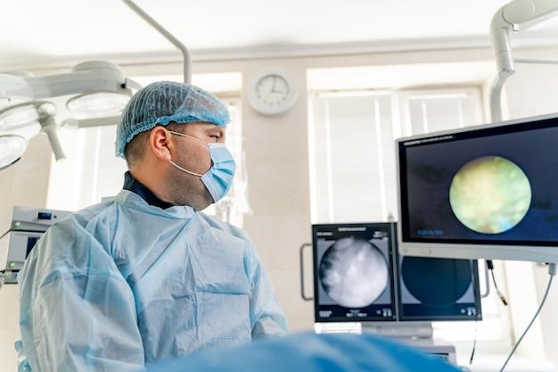 Ablauf der operation operation. chirurg im operationssaal mit operationsausrüstung. medizinischer hintergrund. selektiver fokus auf monitor für trecking-prozess.