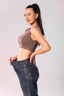 Abnehmen und diätkonzept. slim fit frau zeigt ergebnisse nach fitness und training