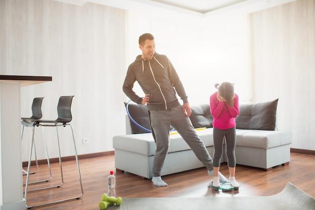 Abnehmen. vater und tochter werden auf einer indoor-haushaltswaage gewogen. lustige und freudige momente, die spaß in der familie haben. diät, richtige ernährung und gesundes lebensstilkonzept