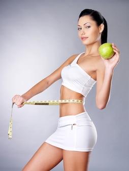 Abnehmende frau misst figur mit einem maßband und hält den apfel. cocnept für einen gesunden lebensstil.