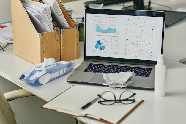 Abnehmende grafiken auf laptop-bildschirm, maske, flasche antiseptikum, packung feuchttücher auf dem tisch des büroangestellten