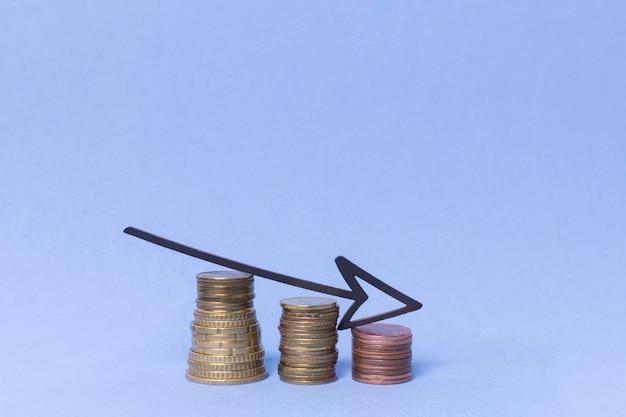 Abnehmende stapel von münzgeld mit pfeil