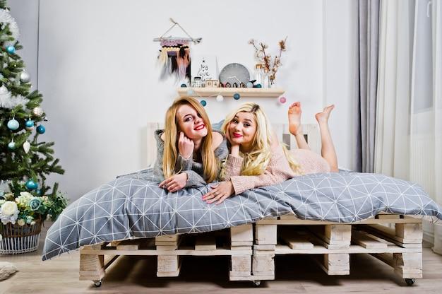 Abnutzung mit zwei elegante blonde mädchen auf dem warmen kittel, der auf bett gegen baum des neuen jahres sitzt.