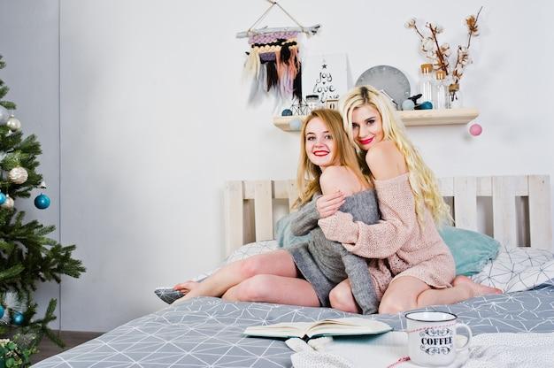 Abnutzung mit zwei elegante blonde mädchen auf dem warmen kittel, der auf bett sitzt.