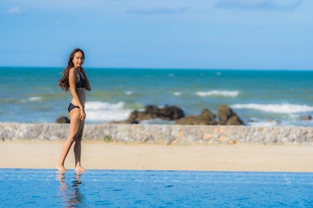 Abnutzungsbikini der schönen jungen asiatischen frau des porträts um swimmingpool im hotelerholungsort fast seeozeanstrand
