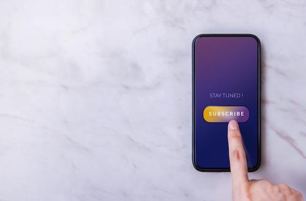 Abonnement und digitales marketingkonzept. draufsicht einer person, die ein smartphone zum abonnieren verwendet