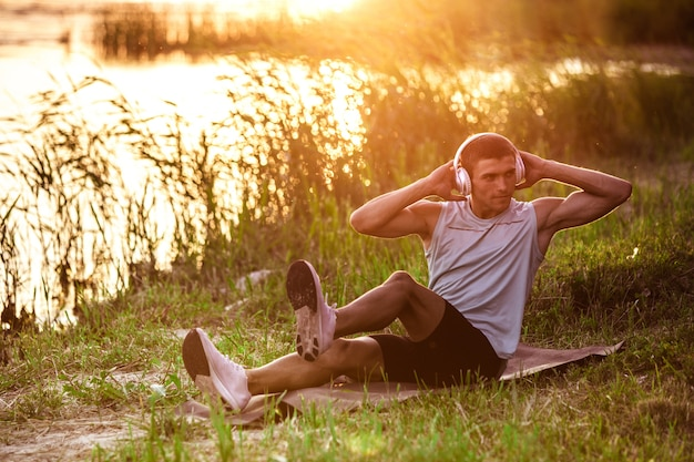 Abs knirscht. ein junger athletischer mann trainiert, trainiert das hören von musik am flussufer im freien.