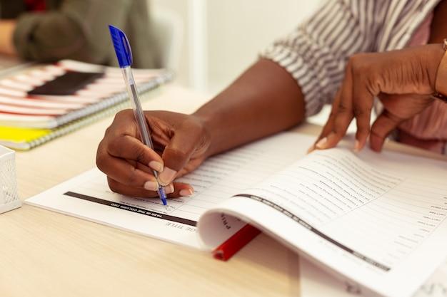 Abschließen der aufgabe. aufmerksamer internationaler student, der am tisch sitzt und tests macht