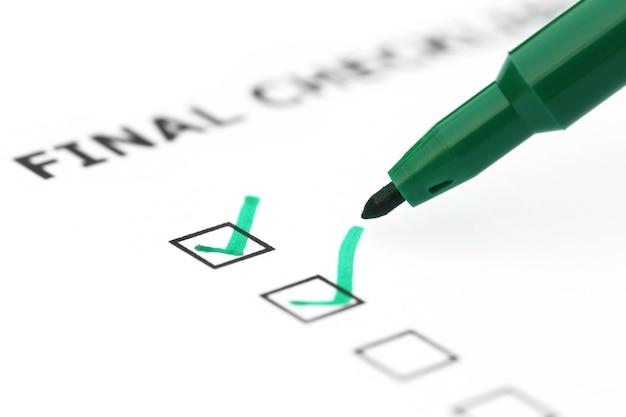 Abschließende checkliste mit grünem stift über weißem papier