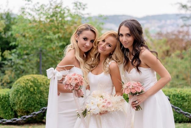 Abschluss der lächelnden braut, im hochzeitskleid tragend, blumenstrauß von rosen halten; zwischen brautjungfer stehen und in die kamera schauen