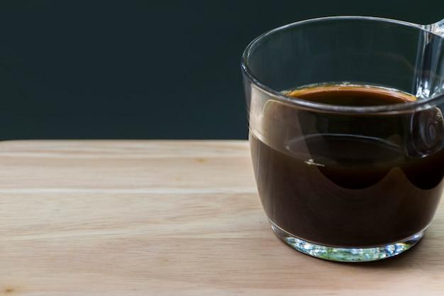 Abschluss des schwarzen kaffeeglases auf dem linken hölzernen brett und verwischen schwarzen grünen hintergrund