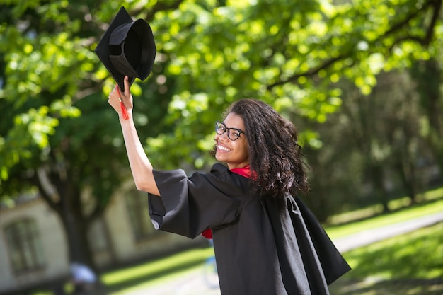 Abschluss. dunkelhaariger absolvent, der sich glücklich und aufgeregt über den abschluss fühlt