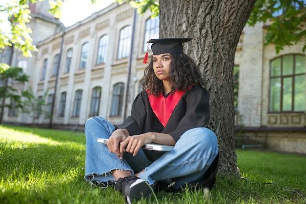Abschluss. ein mädchen im akademischen gewand, das mit einem laptop unter dem baum sitzt